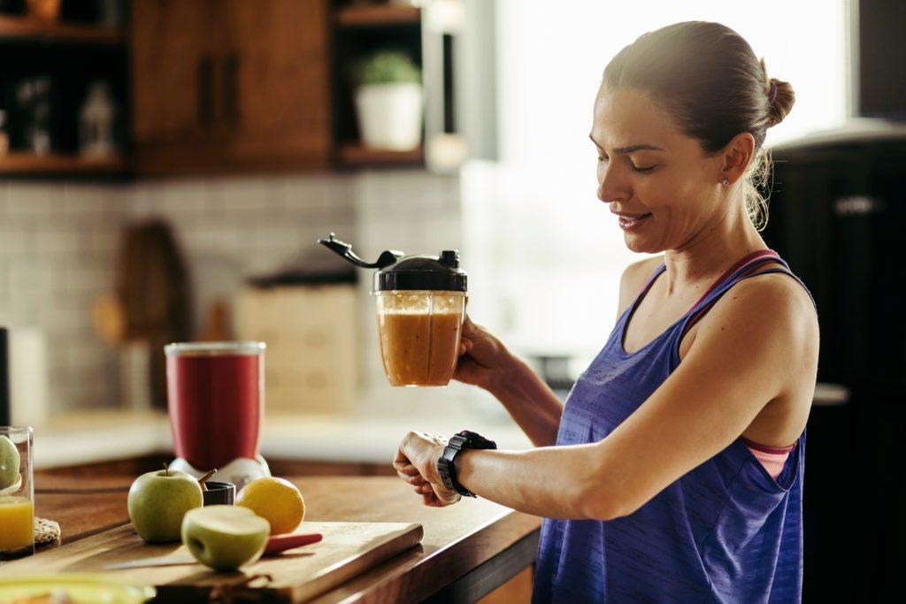 gülen  sporcu kadın elinde ek gıda ile saatini kontrol ediyor